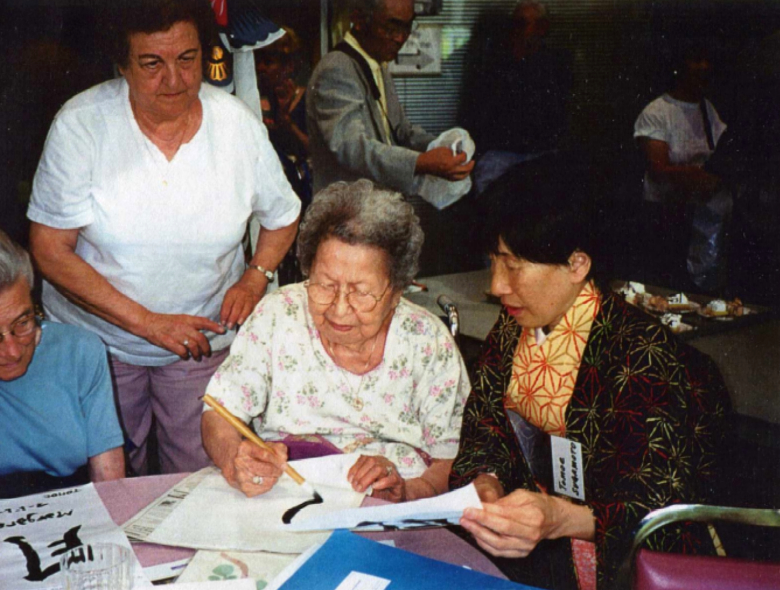 Image of Japanese guest teaching a Surrey resident calligraphy